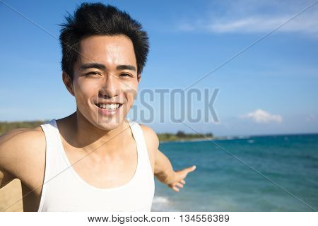 relaxing and smiling young man on the beach