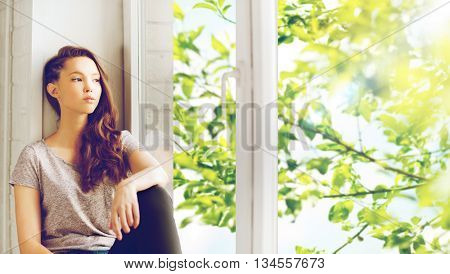 people, emotion and teens concept - sad unhappy pretty teenage girl sitting on windowsill