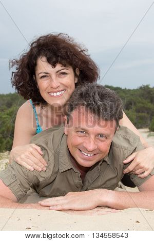 Lovely Middle-aged Couple Smiling At The Beach On The Sand