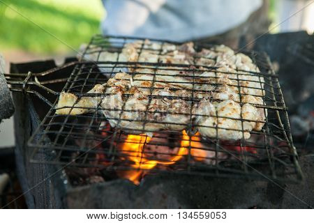 Preparation of meat slices in sauce on fire.