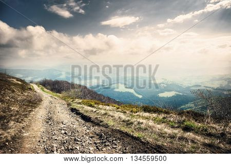 Turning rocky road in mountains under a dramatic sky. Carpathians.