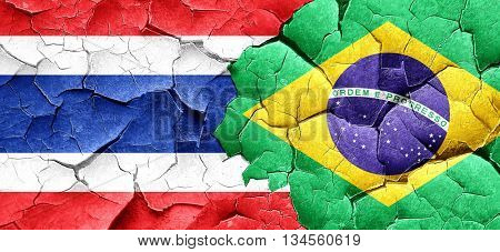 Thailand flag with Brazil flag on a grunge cracked wall