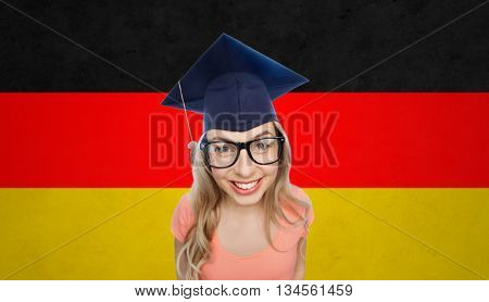 people, graduation and national education concept - smiling young student woman in mortarboard and eyeglasses over german flag background