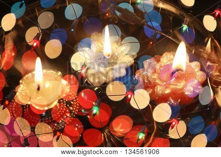 An abstract image of floating candles behind a wire mesh of colorful lights during Diwali festival in India.