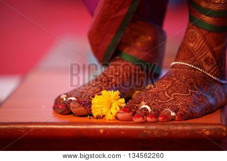 A ritual during a traditional Indian marriage with a marigold flower kept near the brides feet.