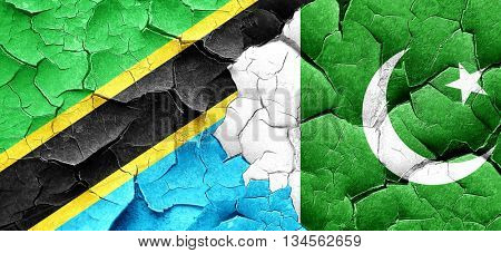 Tanzanian flag with Pakistan flag on a grunge cracked wall