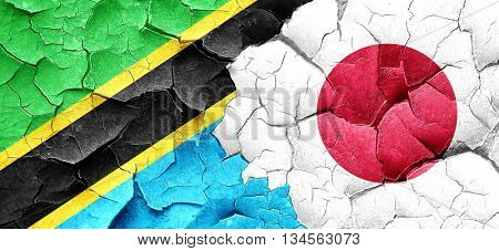 Tanzanian flag with Japan flag on a grunge cracked wall