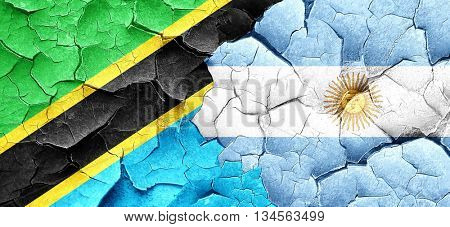 Tanzanian flag with Argentine flag on a grunge cracked wall