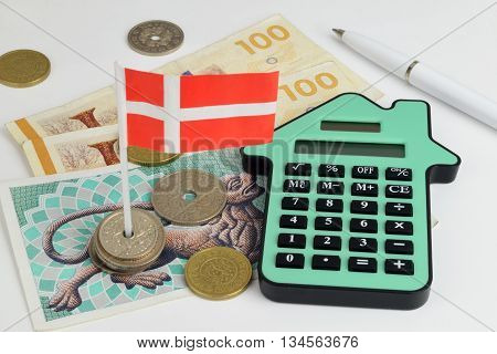 Danish notes and coins with a house shaped calculator to represent property finance.