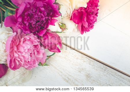 Peony background. Fuchsia, pink and white peonies on white wooden table with place for text. Spring flowers peonies. Happy Mothers Day. Mother's Day greetings card. Mothers Day gift. Copy space.