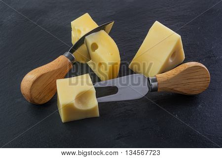 Three pieces of cheese on a black stone slate plate with knife and fork