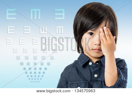 Close up conceptual portrait of little Asian child testing vision with chart.Boy closing one eye with hand and symbol test chart in background.
