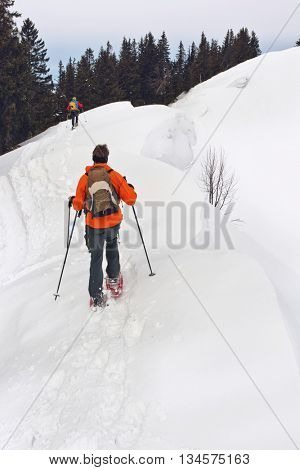 Cross-country skier traversing a snowy mountain slope in alpine scenery in winter wearing a backpack, view from behind with a second person in the distance ahead