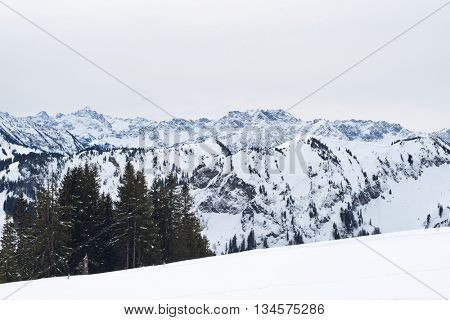 Panoramic vista of snow covered mountains and valleys stretching away into the distance viewed from a snowy summit on a cold bleak winter day