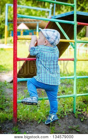 Little toddler climbing the ladder having fun at playground in summer. Cute young boy kid or child playing outdoors on playground. Stylish little baby boy in blue shirt pants and hat. Summer time.