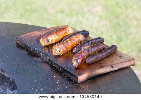 Grilling sausages on cutting board and barbecue grill