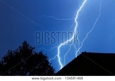 Lightning striking in the city with house and tree in blue sky