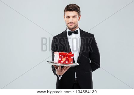 Handsome young butler in tuxedo with bowtie gift box on tray