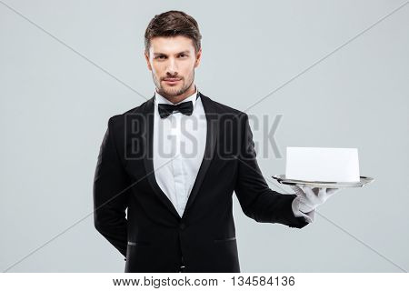 Attractive young butler in tuxedo and gloves holding tray with blank card