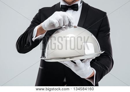 Closeup of serving tray with metal cloche holded by butlers hands in gloves