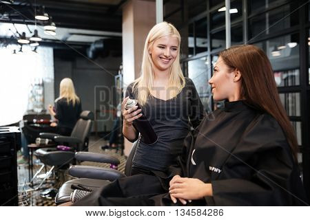 Young hairdresser with hair spray fixating client hairdo at beauty salon
