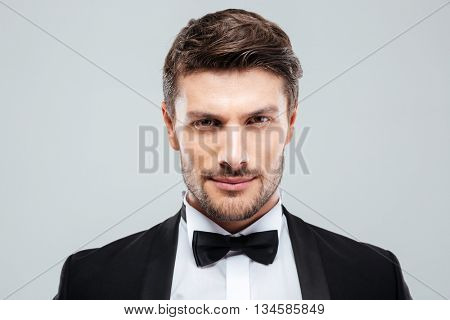 Closeup of attractive confident young man in tuxedo with bowtie