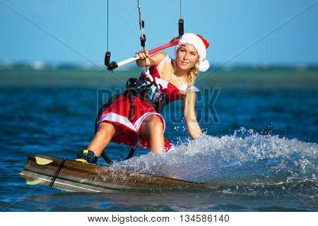 Beautiful young girl on the kite in the costume of Santa Claus. Christmas and New year on a tropical island.