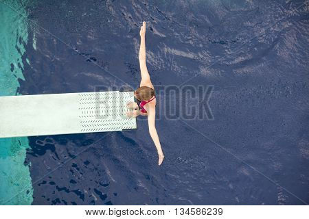 Save Download Preview Lady diver preparing to dive from the springboard into a swimming pool