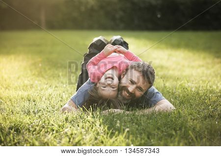 Devoted father and daughter lying on grass enjoying eachothers company bonding playing having fun in nature on a bright sunny day. Parenthood lifestyle childhood and family life concept.