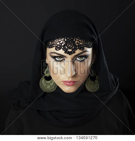 Beautiful Caucasian young woman with black fancy Arabian costume and ornamental jewelry on black background