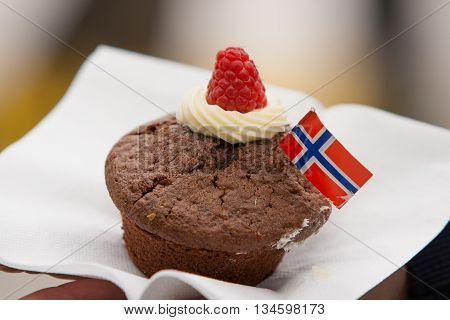 A chocolate cupcake with Norwegian flag on a white napkin. Celebration ofr May 17th.