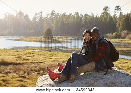Mixed race couple on a rock in countryside looking to camera