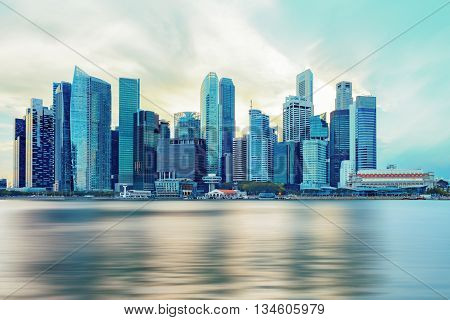 Singapore central quay with water on foreground. Modern city architecture at sunset