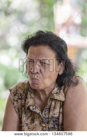 Asian Thai senior female makes a very sour