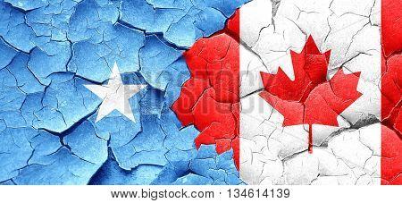 Somalia flag with Canada flag on a grunge cracked wall