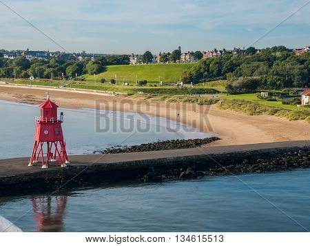 Red-colored lighthouse at The Port of Tyne at North Shields Harbor of Newcastle, England as seen from a ferry ship