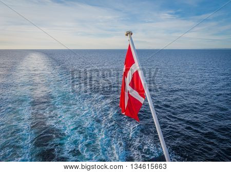Danish flag hanging from the stern of a ferry a ship crossing the north sea