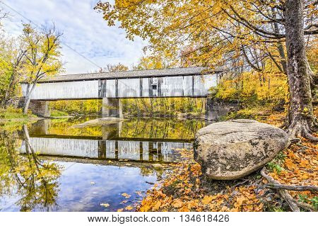 Rustic Darlington Covered Bridge built in 1868 is reflected on Indiana's Sugar Creek surrounded by colorful fall foliage.