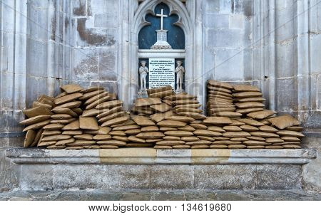 WINCHESTER, UK - FEBRUARY 07: Sandbag objects near wall recess with statues and crucifix at Winchester Cathedral. Winchester Cathedral, Winchester, UK, 07 February 2016.