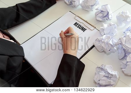 Hands of female writing resume with crumple sheets of papers at the office desk.