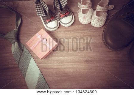 Daddy's boots baby's shoes Textile hearts gift and blue necktie on wooden background .fathers day concept vintage color