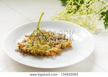 fried elderflower in pancake batter with powdered sugar on a plate on a white wooden table traditional pastry or dessert selected focus narrow depth of field