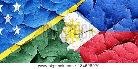 Solomon islands flag with Philippines flag on a grunge cracked w