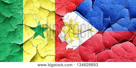Senegal flag with Philippines flag on a grunge cracked wall