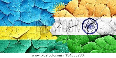 Rwanda flag with India flag on a grunge cracked wall