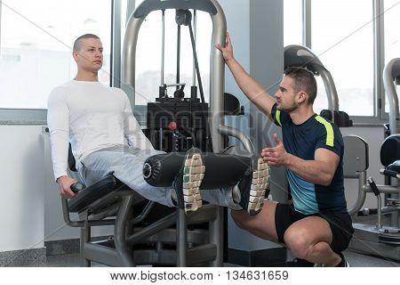 Gym Coach Helping Youg Man On Legs