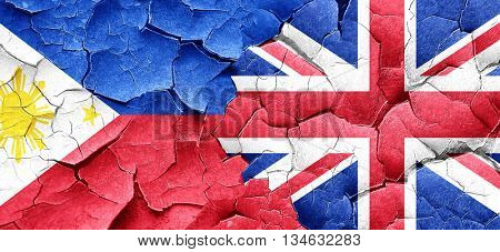 Philippines flag with Great Britain flag on a grunge cracked wal