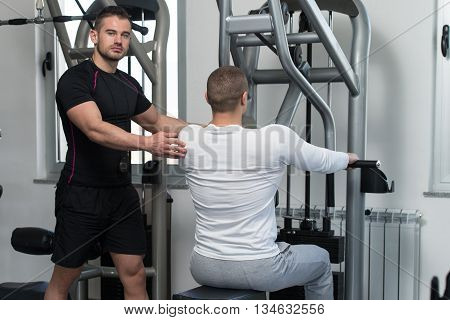 Gym Coach Helping Young Man On Back Exercise