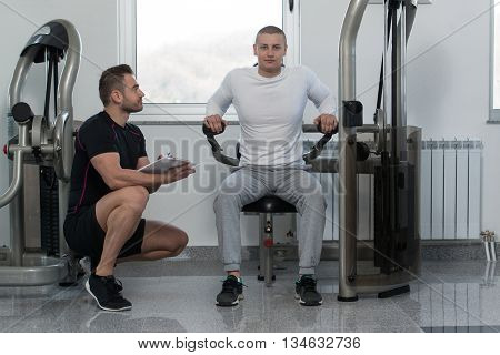 Trainer Writing On Clipboard While Man Training Triceps
