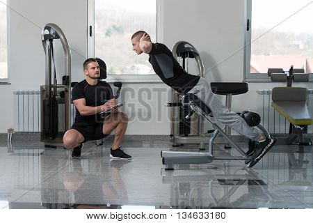 Trainer Writing On Clipboard While Man Training Back